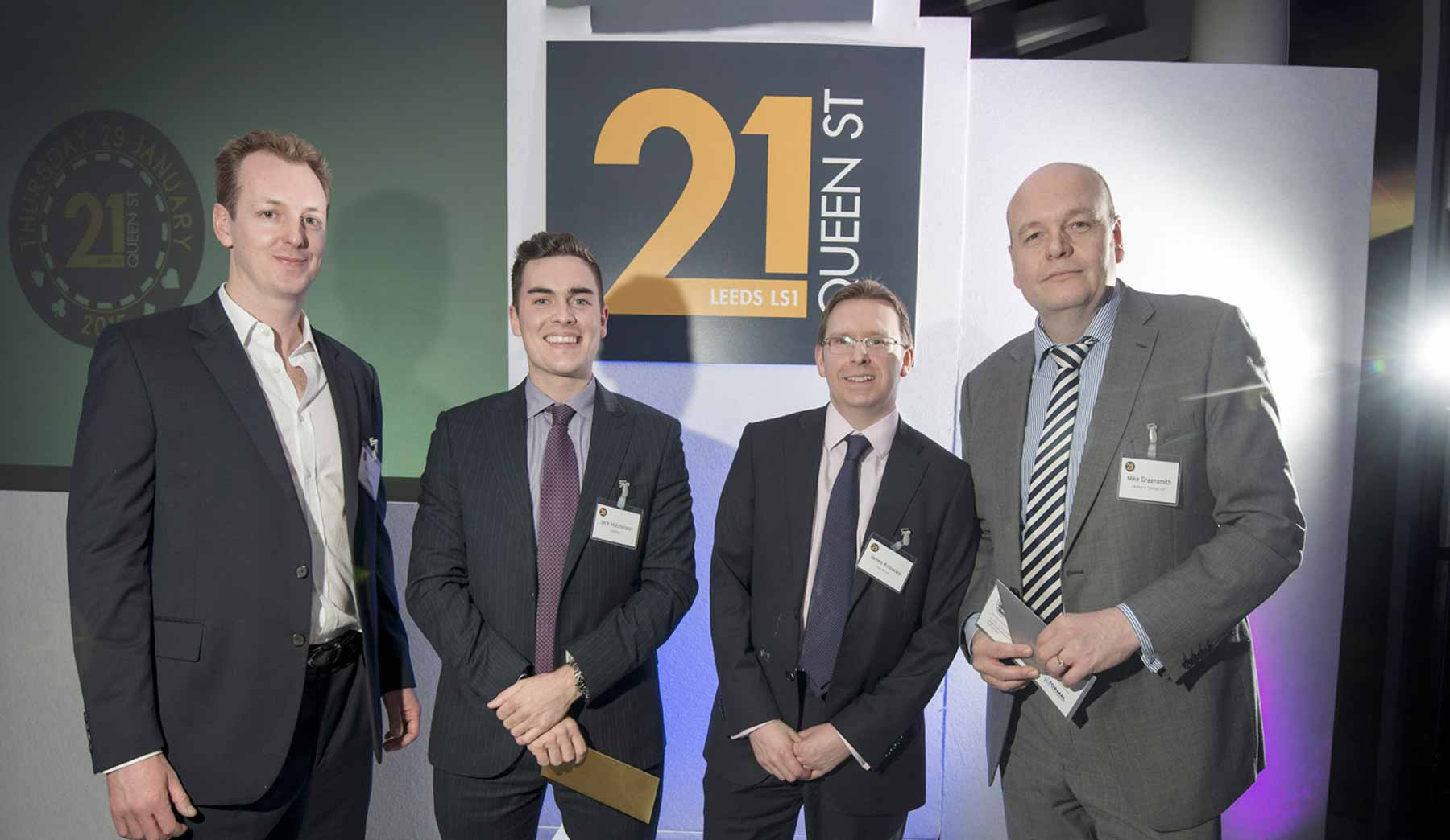 Four men stood in front of a 21 Queen Street logo